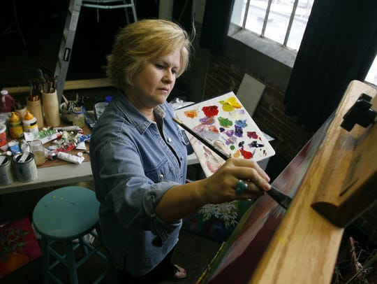 Artist Gayla Hodson works on a piece in her studio