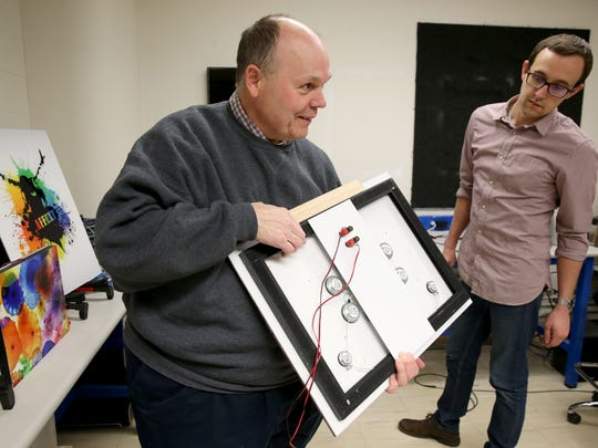 University of Rochester professor Mark Bocko, with a prototype flat-panel speaker that he and grad students Dave Anderson, right, and Mike Heilemann (not pictured) have developed.
