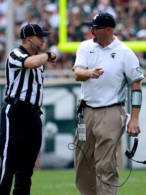 MSU offensive line coach Mark Staten has some words for a referees Saturday, September 26, 2015, during the Spartans 30-10 win over Central Michigan.