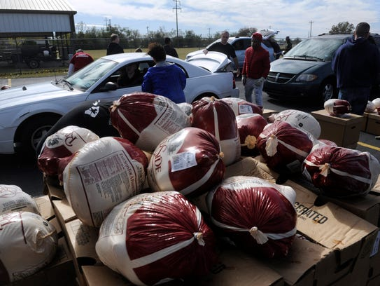 Frozen turkeys are stacked on boxes at VFW Post 6873 Saturday, while in the background cars are loaded with meals by volunteers.