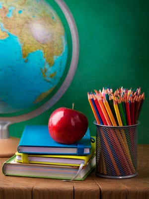 Stack of books, red apple, globe and pencils.
