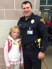 Evesham police officer Brian Libetti (right) stands with second grade student Olivia Shoemaker in front of Rice Elementary School. Libetti is a School Resource Officer at Rice and walks Olivia into the school each morning and to her classroom. She used to cry each morning before he began this ritual. Now her tears have disappeared.