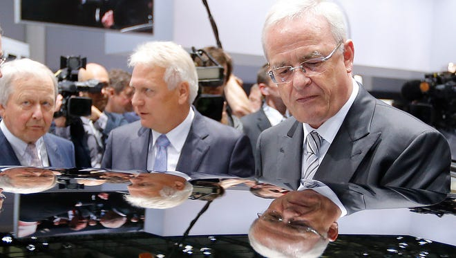 In this May 5, 2015 file photo, Volkswagen CEO Martin Winterkorn, right, is reflected at the roof of a car during a tour around a fair hall prior to the annual shareholder meeting of the car manufacturer Volkswagen in Hannover, Germany.