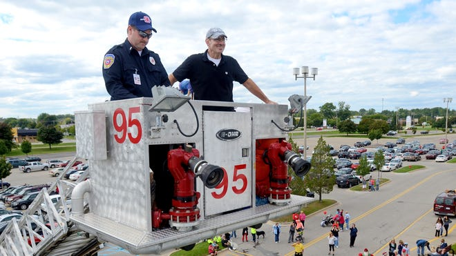 WSAQ morning show host, Chuck Santoni, is hoisted to the roof by the Fort Gratiot Fire Department Sunday to kick off the the annual Walk for Kids' Sake and Roof Sit at the Birchwood Mall.