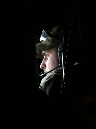 An air force airman looks through a window of a C-130 transport aircraft on the way to Kabul, Afghanistan on Jan. 23, 2018.