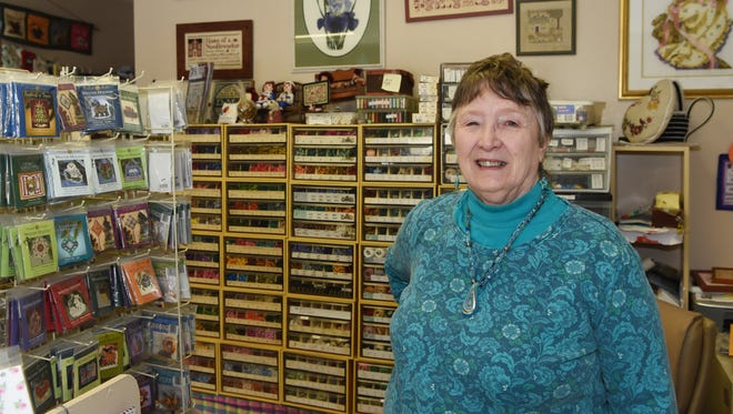 Pat Athanas, owner of Deer Hill Farm Cross Stitching, stands behind the counter of her store in Hyde Park.