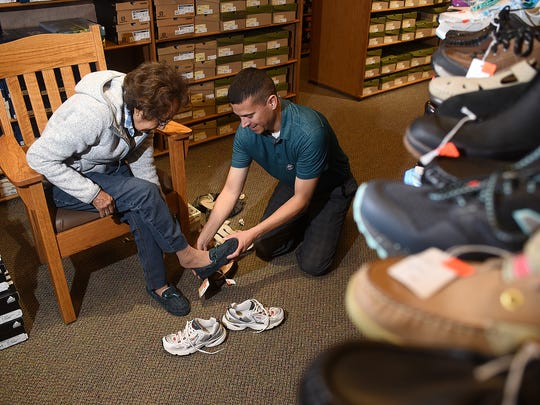 Laura Lee Lineberry, of Zuni, left, tries on some shoes with the help of Reuben Morales during Small Business Saturday on Saturday at Brown's Shoe Fit Co. in downtown Farmington.