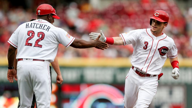 Cincinnati Reds second baseman Scooter Gennett (3) high fives Cincinnati Reds third base coach Billy Hatcher (22) after hitting a two-run home run in the first inning during an interleague baseball game between the Chicago White Sox and the Cincinnati Reds, Tuesday, July 3, 2018, at Great American Ball Park in Cincinnati.