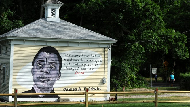 "A mural depicting novelist, poet and activist James Baldwin and featuring one of his quotes covers the side of a carriage house on Route 6A in Barnstable. It was painted by Joe Diggs and Jackie Reeves at the request of the property owners. ""It's an opportunity to learn and look at things from a different perspective,"" owner David Munsell said."