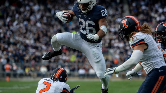 Penn State Nittany Lions running back Saquon Barkley (26) leaps over Illinois Fighting Illini defensive back V'Angelo Bentley (2) on his way to a touchdown as Penn State beat Illinois 39-0 at Beaver Stadium on Saturday, October 31, 2015. Jeremy Long -- Lebanon Daily News