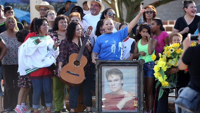 Fans sing songs from Mexican Singer/Songwriter Juan Gabriel as they wait for the hearse containing his remains to pass into Juarez from the Stanton Street Bridge Saturday in downtown El Paso.