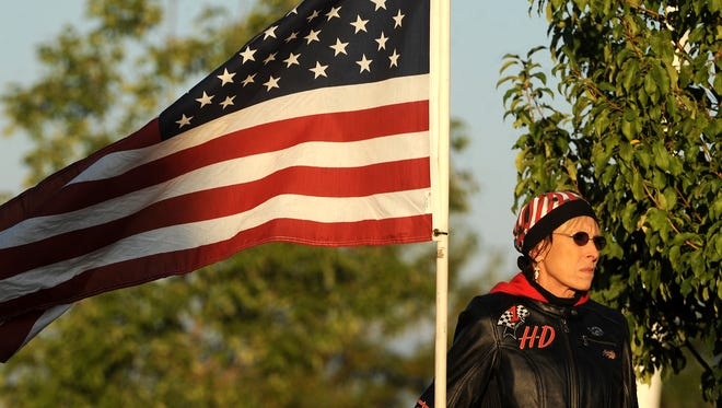 Patriot Guard Rider Deborah Rice welcomes veterans with a flag on Sunday, Sept. 9, 2012, as they enter the Embassy Suites Hotel and Conference Center in Loveland.