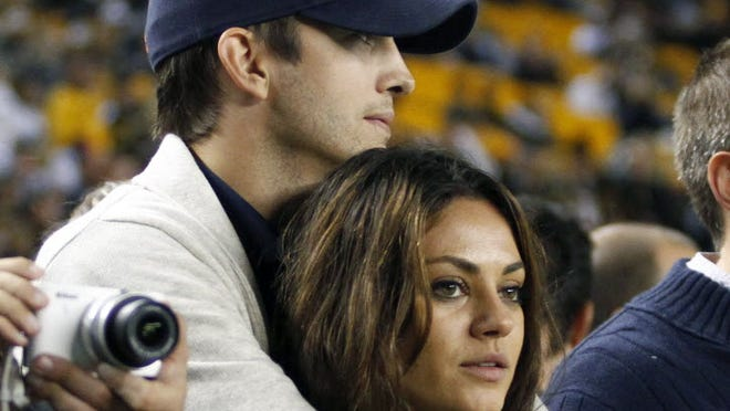 Congratulations Mila and Ashton on your engagement! Here's a look back at the lovebirds from 'That '70s Show' to now. Here, they cuddle during a basketball game on Sept. 22, 2013.