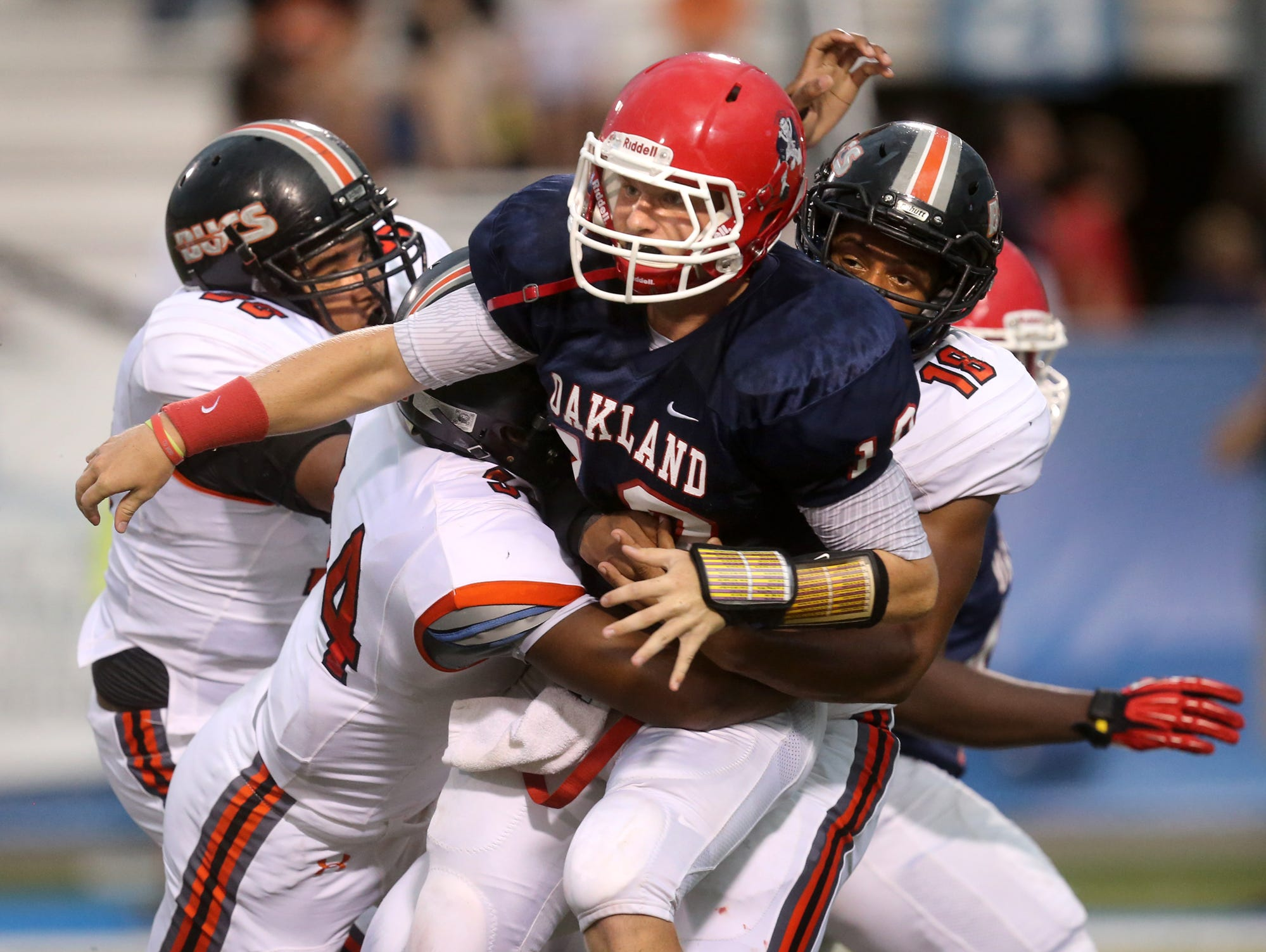 Oakland's quarterback Brendon Matthews (10), gets tackled by Hoover players at the Middle Tennessee Classic at MTSU's Floyd Stadium, on Saturday, Aug. 22, 2015.