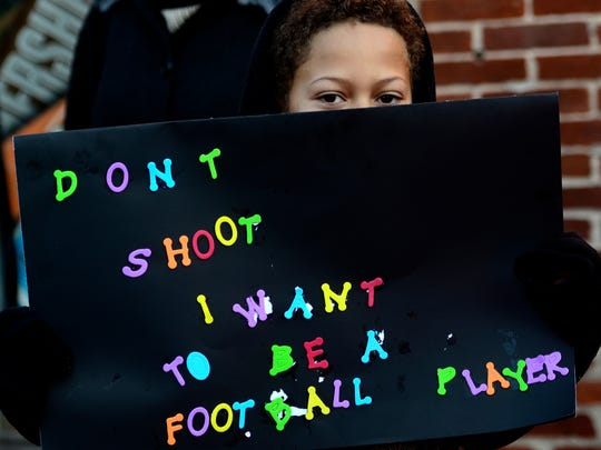 Jean Pierre Larue, 10 of York City, holds a sign during