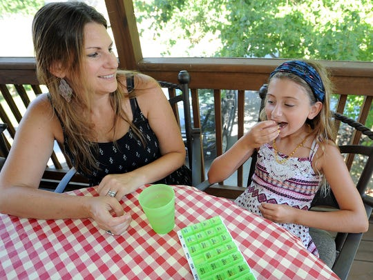 Rylie Maedler, 10, takes a cannabis oil pill on Wednesday