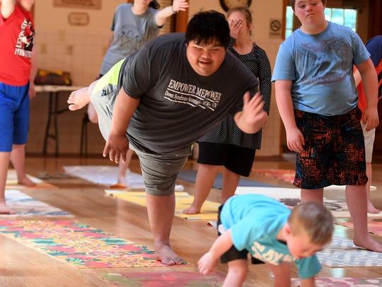 Bernado Flores does a yoga pose during Imaginarium