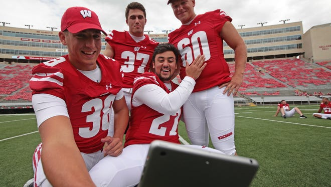UW  punter P.J. Rosowski (38) holds the iPad for the special teams unit  as they answer a  group question-  Andrew Endicott (37)  Rafael Gaglianone (27) and Connor Udelhoven (6) during the 2016 Wisconsin football media at Camp Randall Stadium Sunday, August 7, 2016.