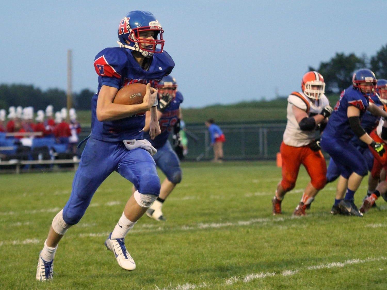 Highland quarterback Max Schreiber scrambles for major yardage against Heath High School.
