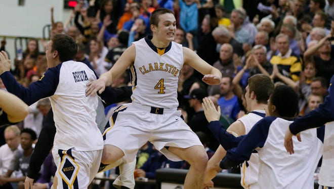 Clarkston's Andrew Myers runs to his players off the bench celebrating after the clock ran out in their 63-58 win over Dakota in MHSAA boys regional finals basketball game on Wednesday, March 18, 2015 in Troy.