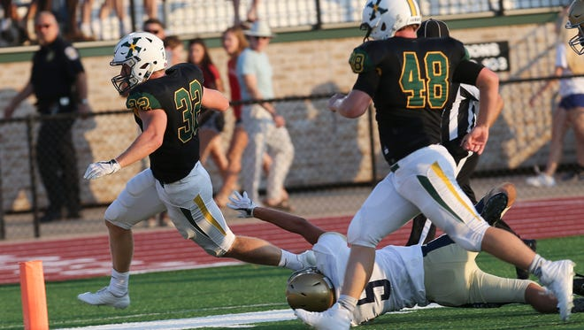 St. X's Brett Metzmeier (32) slipped a tackle by Indianapolis Cathedral's Bo Sanders (5) to score their first touchdown at St. X.Aug. 18, 2017