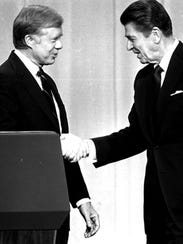 Jimmy Carter and Ronald Reagan shake hands on Oct.
