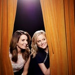 Tina Fey, left, and Amy Poehler return for a second year as Golden Globe hosts Sunday.
