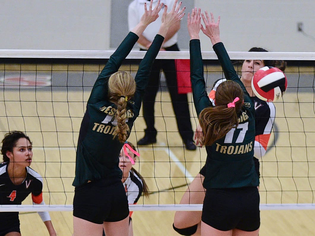 Iowa City West's Ali Tauchen (10) and Maddie Fay (17) reach high to block a West Des Moines Valley spike at the Class 5A-Region 5 regional finals held at Newton High School on Tuesday, Nov. 4, 2014.