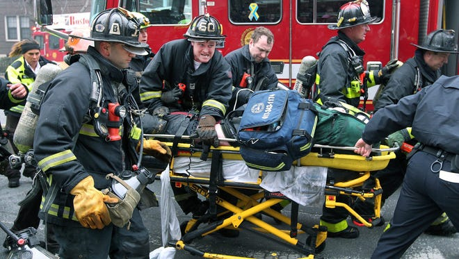 A handout picture provided by the Boston Globe shows Boston Fire Department firefighters working on a fellow firefighter as he is rushed to an ambulance after being injured while fighting a nine alarm fire that broke out in a building at 298 Beacon Street in the Back Bay neighborhood of Boston on March 26, 2014. Two firefighters were killed fighting the fire and 18 were transported to the hospital.
