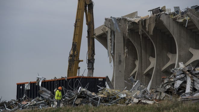 A worker walks past piles of rubble while deconstruction continues at Hughes Stadium on Monday, April 16, 2018, in Fort Collins, Colo.