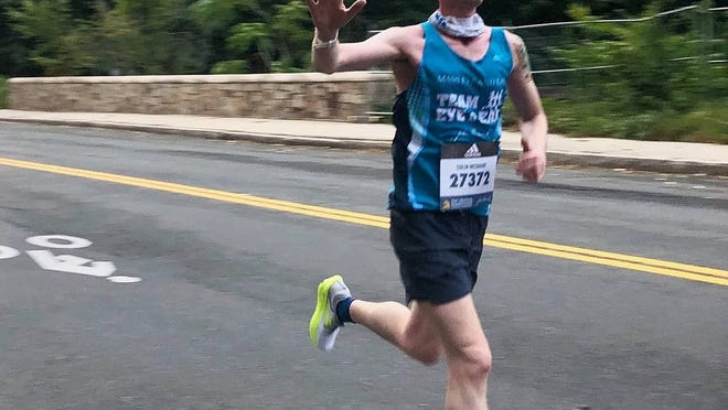 Colin McShane of Fitchburg waves as he powers through the roads of his native Winchester while completing his virtual Boston Marathon.