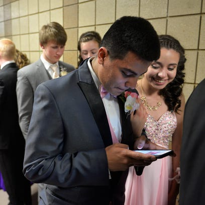 Junior Omar Reyes checks a text from his brother as his date, Pam Hernandez, looks on as they wait in line for the start of Melrose's grand march.