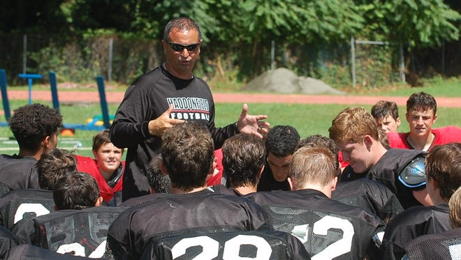 Haddonfield coach Frank DeLano addresses his team following a recent practice. The Bulldawgs open their regukar-season schedule Sept. 8 against Collingswood.