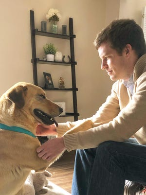 Adam Schwiebert and the 1-year-old Labrador he adopted in March share a special moment in their Hilliard home. These moments won't be as frequent with Schwiebert and his wife headed back to the office in coming weeks.