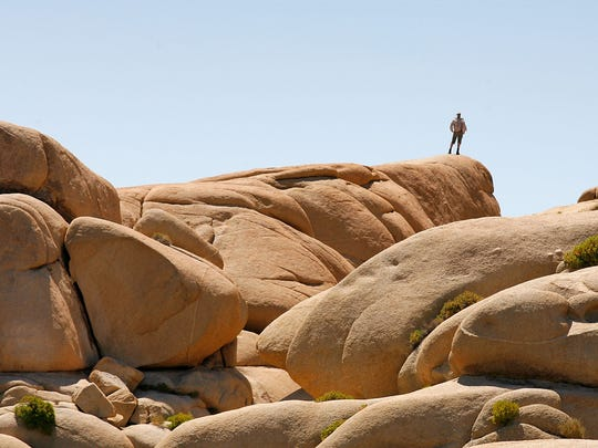 A vistitor takes in the view atop the Jumbo Rocks area in Joshua Tree National Park.  7/22/11