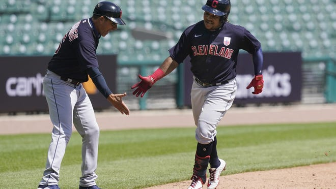 Indians third base coach Mike Sarbaugh congratulates Jose Ramirez after a solo homer during the fifth inning Sunday, Aug. 16, 2020, against the Tigers in Detroit.