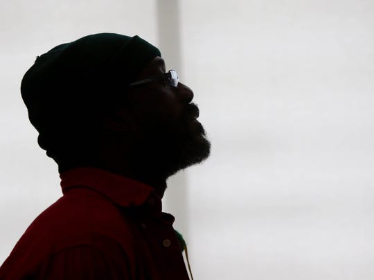 Frederick Fernando Foster listens to Jeffrey B. Perry speak about race during an event at the Wilmington Library on Friday.