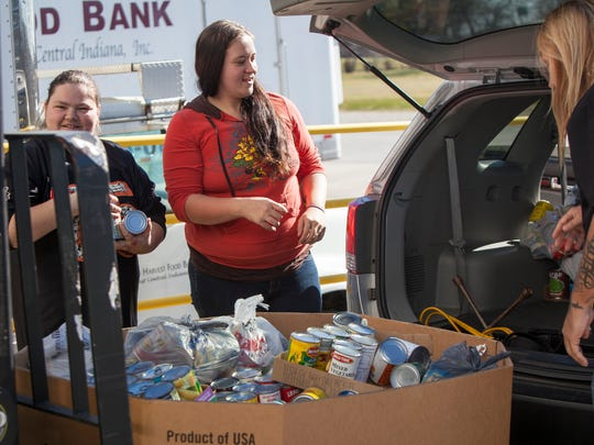 Kimberly Cook, left, along with Cassie and Micheal Keihn and several others help unload nearly 1200 lbs. of food being donated to the Second Harvest Food Bank of East Central Indiana Monday afternoon. Second Harvest was one of several charities funded by the Organ Trail Halloween house.