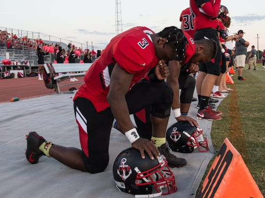 James M. Bennett's SaQuan Cotton (3) and Diondre' Carter (2) pray before the start of a game against Parkside on Friday, Oct. 6, 2017.