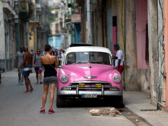 A young woman takes pictures of a vintage car in Havana