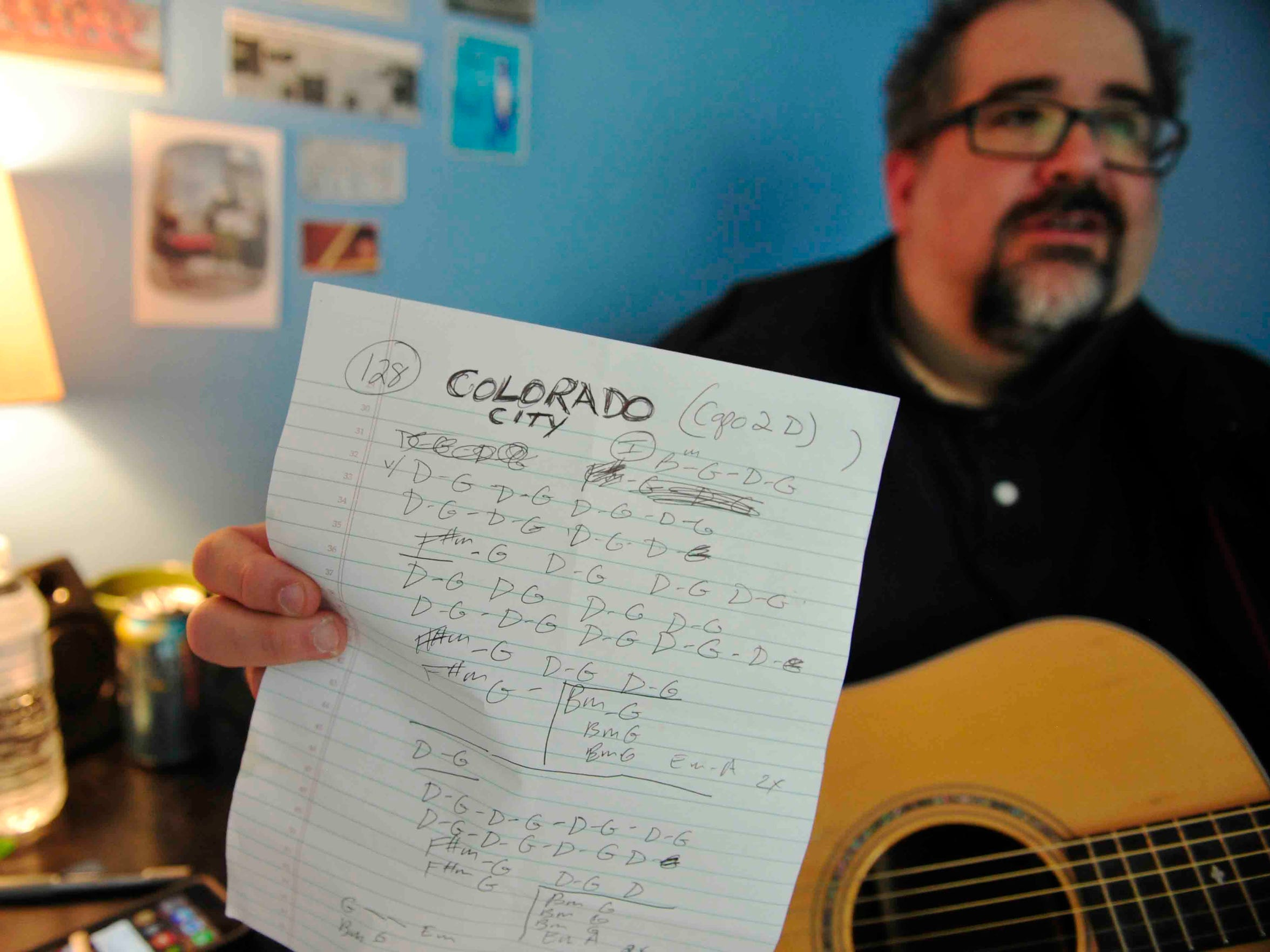 Jim Reilley holds the key sheet for the New Dylans song 'Colorado City' while practicing at his Berry Hill songwriting office on July 28, 2014.
