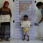A Rohingya woman and a child from Burma are photographed during police identification procedures at a newly set up confinement area in Bayeun, Aceh province, Indonesia.