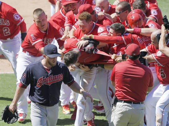 Team members mob Los Angeles Angels' Taylor Featherston, center, after he scored on a wild pitch to win the game as Cleveland Indians relief pitcher Cody Allen, left, walks off the field during the ninth inning of a baseball game, Wednesday, Aug. 5, 2015, in Anaheim, Calif. The Angels won 4-3. (AP Photo/Mark J. Terrill)