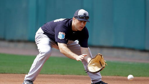 New York Yankees infielder Dustin Ackley fields a ground ball during warm ups before a spring training baseball game against the Atlanta Braves, Wednesday, March 30, 2016, in Kissimmee, Fla.