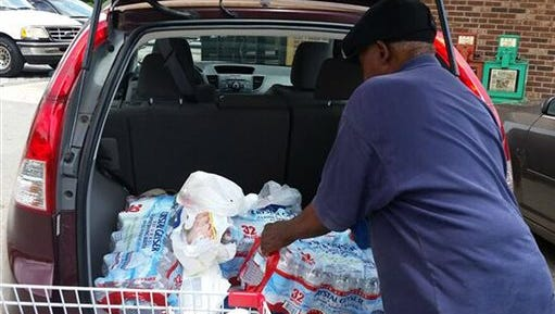 Lee Allen loads bottled water into his vehicle outside the Supervalu Grocery Store in Courtland, Ala., on Friday, after a local utility warned residents not to drink the tap water because of chemical contamination. Allen said purchasing water is expensive and inconvenient but necessary after the announcement.