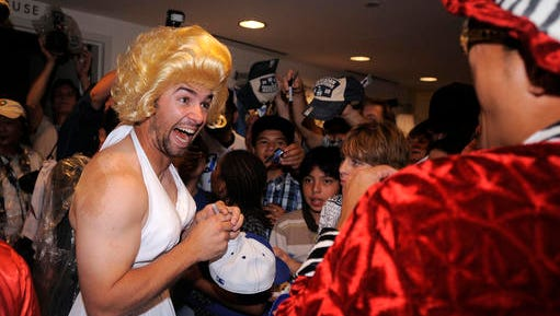 FILE - In this Sept. 25, 2008, file photo, Los Angeles Dodgers' Blake DeWitt, left, laughs at Hiroki Kuroda as they sign autographs while wearing costumes as part of rookie hazing, after their Major League Baseball game against the San Diego Padres, in Los Angeles. That baseball hazing ritual of dressing up rookies as Wonder Woman, Hooters Girls and Dallas Cowboys cheerleaders is now banned. Major League Baseball created an Anti-Hazing and Anti-Bullying Policy that covers the practice. As part of the sport's new labor deal, set to be ratified by both sides Tuesday, Dec. 13, 2016, the players' union agreed not to contest it.