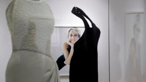 "A photograph by Mario Testino of Diana, Princess of Wales is seen through two dress that she wore during a media preview of an exhibition of 25 dresses and outfits worn by Diana entitled ""Diana: Her Fashion Story"" at Kensington Palace in London, Wednesday, Feb. 22, 2017."