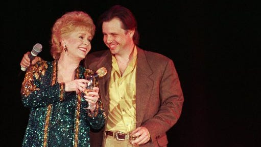 """FILE - In this April 1, 1997, file photo, Debbie Reynolds, left, celebrates her 65th birthday on stage as her son, Todd Fisher, presents her with a cake following her evening variety show, at the Debbie Reynolds Hotel in Las Vegas. Fisher told Entertainment Tonight for an interview published online on March 22, 2017, that Reynolds set him up """"for her leaving the planet"""" the day his sister and Reynolds' daughter Carrie Fisher died in December 2016."""