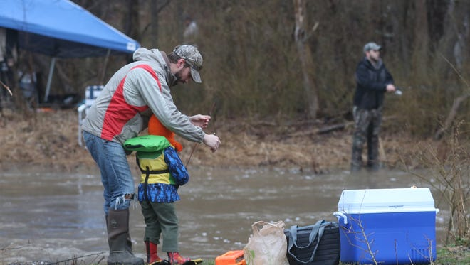 Jonathan Missel of Mendon helps his son, Paxton, with his line during the 14 Annual Riedman Foundation Opening Day Trout Derby at Powder Mills Park.  This was the first time for both of them in the fishing derby.