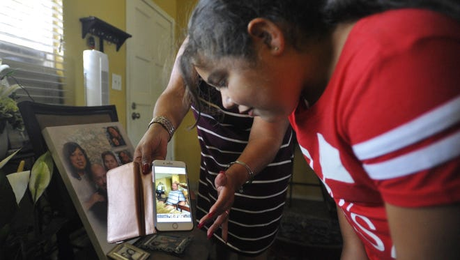 Jazlyn Fisher, 8, watches a video of her father, Eric Fisher, who was killed Saturday, May 27.